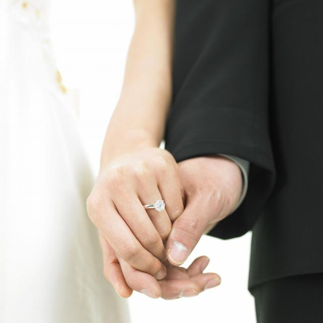 a bride wearing a wedding ring and a bridegroom holding her hands.