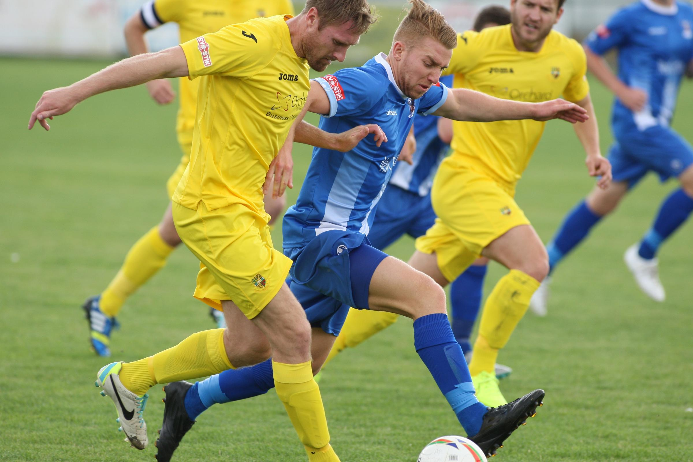 AFC Totton's Craig Feeney (blue)