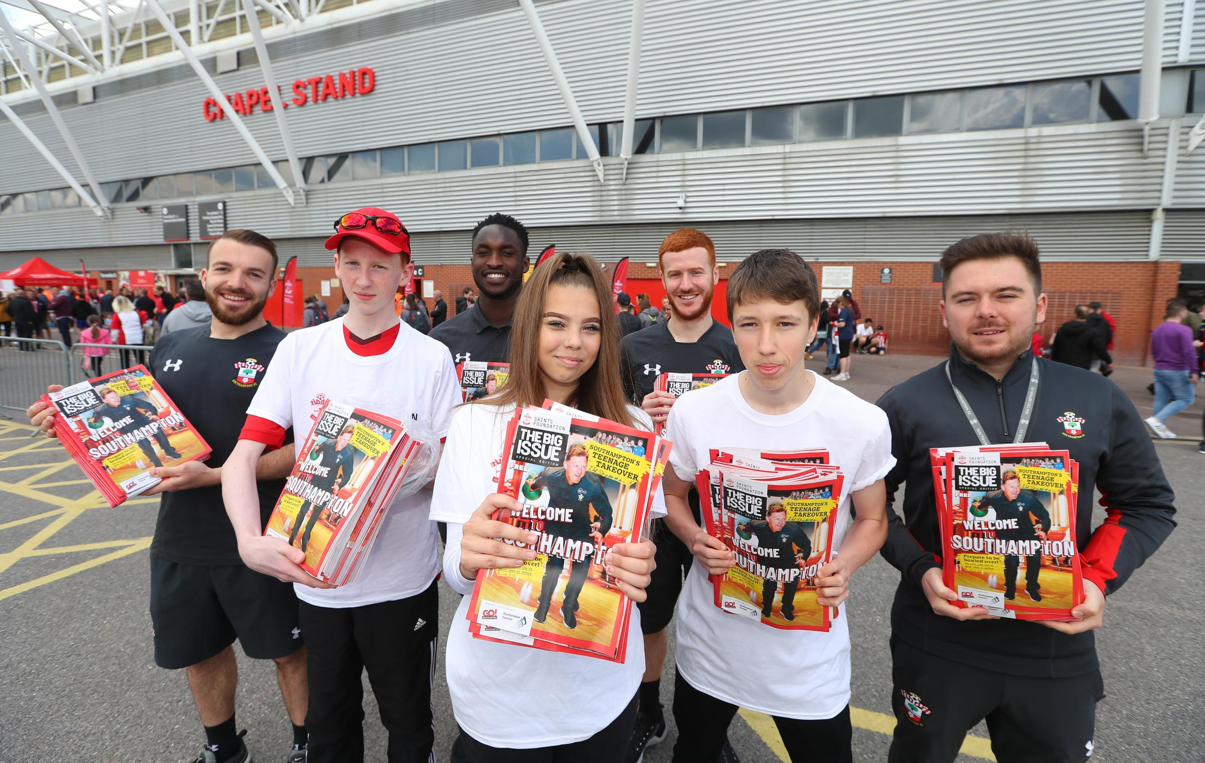 Southampton school pupils with members of the Saints Community champions handing out copies of the Big Issue at St Mary's Stadium